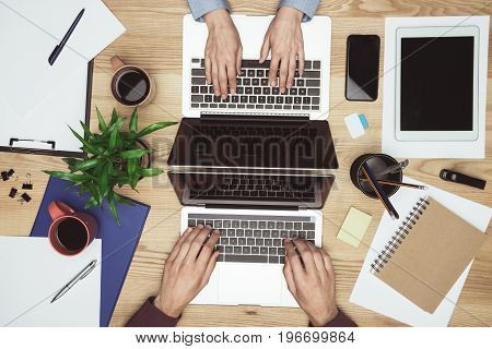 Top View Of Businesspeople Working And Typing On Laptops At Workplace With Gadgets And Office Suppli