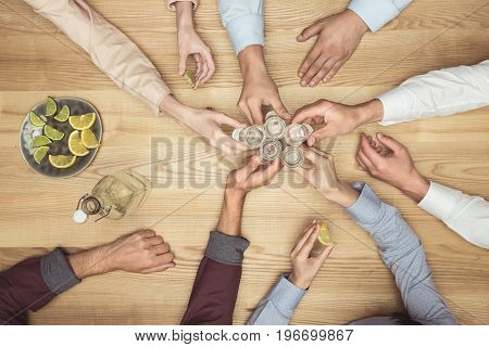Top View Of Friends Hands With Tequila Shots On Wooden Tabletop