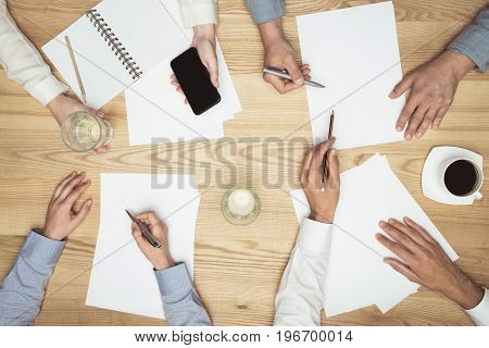 Top View Of Businesspeople On Meeting With Documents And Smartphone At Workplace