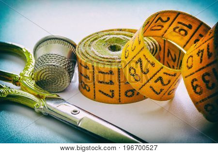 Sewing measuring tape scissors and thimble accessories for needlework and sewing hobby white background retro style