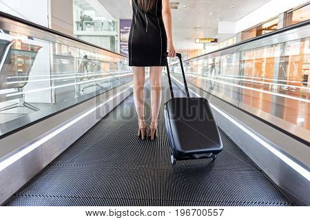 Business and travel. Close up of legs of graceful lady is standing with suitcase on modern moving walkway at international airport
