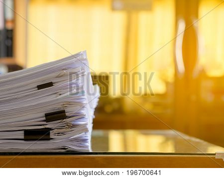 Stack of paper files on work desk in office. Flare light.