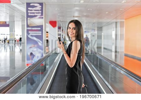 Enjoying travel. Portrait of happy young businesswoman is expressing gladness while using mobile phone. She is looking at camera with joy while standing on moving walkway in modern airport