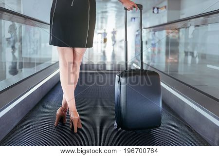 Business trip concept. Close up of legs of elegant graceful woman is holding suitcase while standing on escalator at modern airport