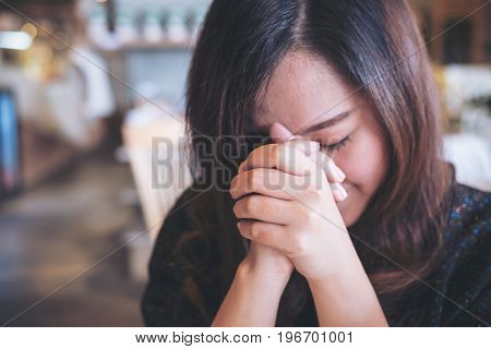An Asian woman close her eyes to praying and wishing for a good luck