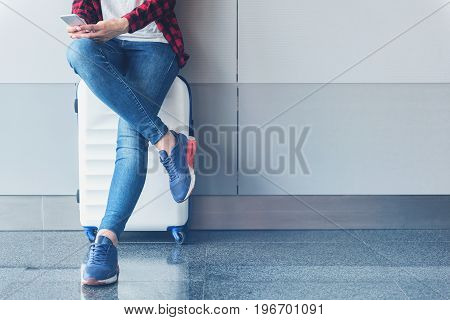Sharing interesting news. Close up of crossed legs of girl who is sitting on suitcase in airport while sending message using mobile phone. Copy space in the right side