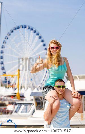 Relationship goals summer love concept. Man giving girlfriend piggyback ride on marina woman showing thumb up gesture.