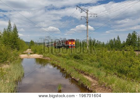 Red-yellow locomotive on the railway in South Yakutia Russia