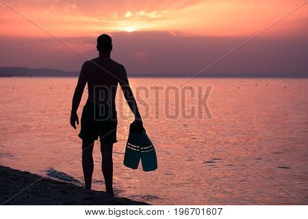 Silhouette of swimmer holding flippers on beach during the sunset over sea. Summer vacation and water sports concepts.