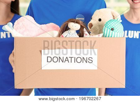 Young volunteers with box of donations indoors, closeup