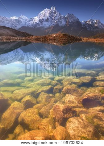 Nepal, Manaslu Region, a reflection in the Bimtang lake (3,680 m) of the Phungi peak (6,538 m) in the centre and the Mansiri Himal (7,059 m) at the left side.