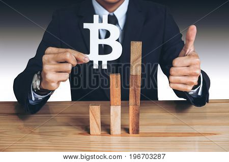 Financial growth concept Businessman holding showing bitcoin symbol concede Rise of price and the continued growth of the business. wooden block of the growth of income in bitcoins.