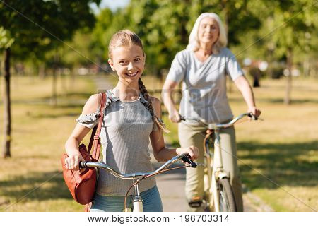 Happy childhood. Positive pretty girl riding a bicycle and standing in the park while her grandmother expressing joy in the background