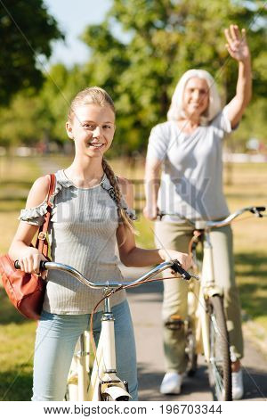 Pleasant weekend. Cheerful teenager girl riding a bicycle in the park while her grandmother waving her hand in the background