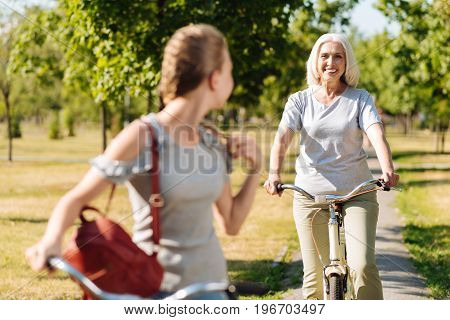 Follow me. Positive senior woman riding a bicycle while riding behind her granddaughter in the park
