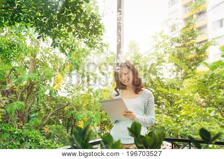 Young Attractive Sweet Girl With Notepad On A Veranda. Spring Mood.