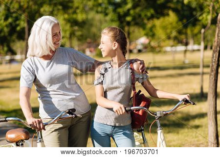 My dear. Positive lovign senior woman embracing her teenager granddaughter while resting in the park and riding bicycles