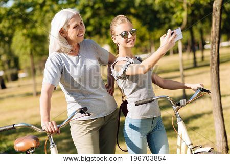Memorize this moment. Cheerful teenage girl making selfies with her grandmother and resting in the park while riding bicycles together