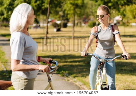 Its a good day. Cheerful pretty teenager girl smiling and riding a bicycle while resting in the park with her grandmother