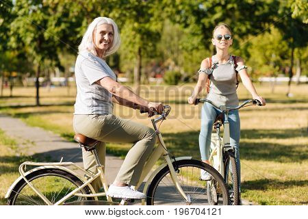 Pleasant time outdoors. Cheerful beautiful senior woman riding a bicycle and expressing gladness while resting in the park with her granddaughter