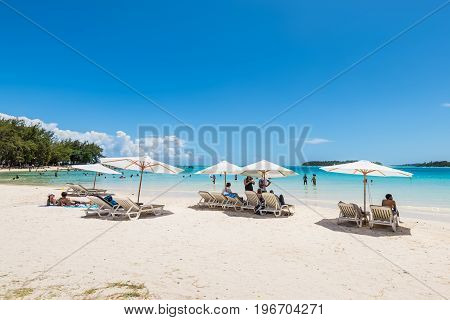 Blue Bay Mauritius - December 27 2015: People relax under umbrellas and in the sun on the tropical Blue Bay beach Mauritius Island. Idyllic travel background.