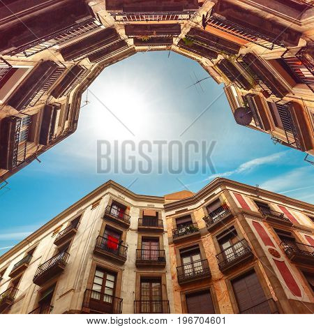 Backstreet with unusual curved houses, bottom-up view with sun in a blue sky, Carrer de Milans in Barcelona, Catalonia, Spain