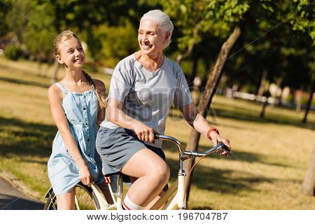 Positive atmosphere. Delighted aged smiling senior woman riding her granddaughter in the park while resting together in the park