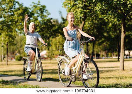 Enjoy the weather. Positive smiling girl riding bicycles with her graddaughter and expressing gladness in the park