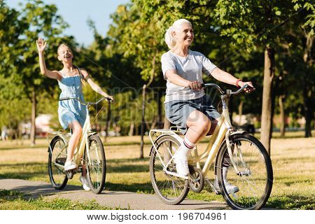 Happiness in mind. Cheerful smiling delighted senior woman riding bicycles with her granddaughter in the park while spending weekend together