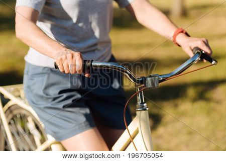 My hobby. Pleasant sporty woman holding handlebar and riding bicycle while rresting in the park