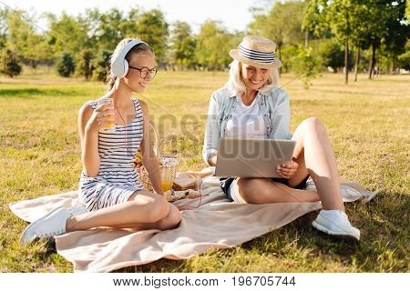 Modern way of life. Cheerful smiling teenager girl listening to music and resting in the park while enjoying picnic with her grandmother