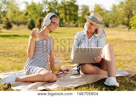 Modern technologies. Positive delighted little girl resting in the park with her senior grandmother while using laptop together and surfing the internet