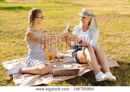 Here you are. Positive delighted teenager girl giving headphones to her smiling grandmother while enjoying picnic together in the park