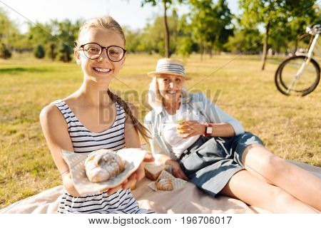 That is for you. Cheerful cute teenager girl sitting on the blanket with her grandmother and enjoying picnic together in the park