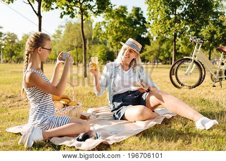 Rememeber it. Cheerful senior woman holding croissant and drinking juice while her granddaughter talking photos of her on a picnic