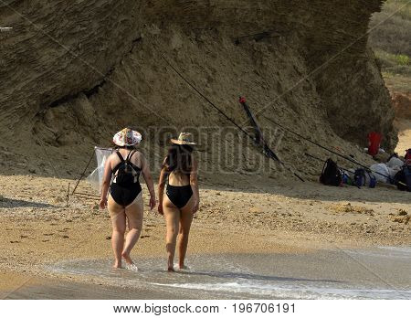 Two women in bathing suits are walking on the beach