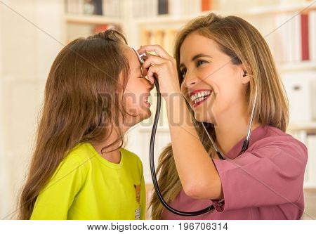 Young pretty girl smiling while a beautiful smiling doctor examining with a stethoscope in her head in a office background.
