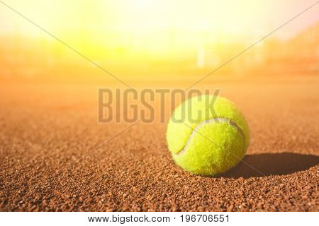 Yellow tennis ball on a clay court.