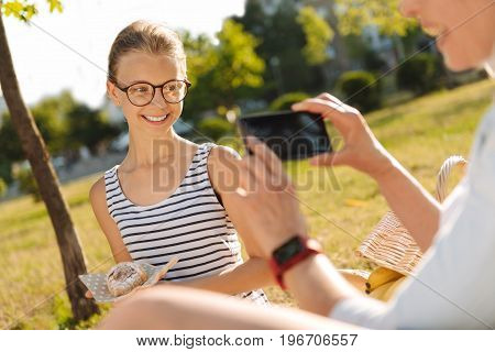 I baked it myself. Cheerful smiling cute girl holding a croissant and posing in front of the camera while her granny taking photos of her on a picnic
