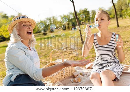 Catch it. Positive delighted woman sitting on the blanket with her cute granddaughter while blowing soap bubbles and enjoying weekend together