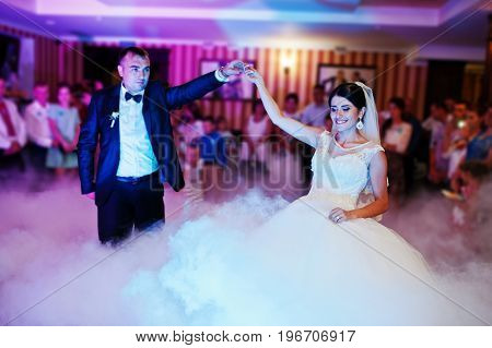 Beautiful Couple Dancing In The Restaurant With Different Lights And Smoke On Their Wedding Day.