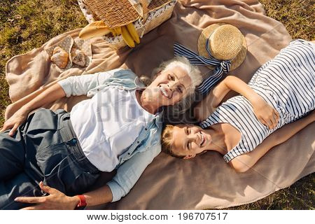 Nice rest. Positive delighted smiling senior woman lying on the blanket with her granddaughter while enjoying a picnic together