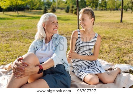 Sincere relations. Positive smiling senior woman sitting on the blanket and resting in the park with her cute granddaughter while looking at each other