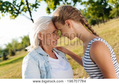 My heir. Positive loving senior woman smiling and standing with her granddaughter head ot head while resting together in the park