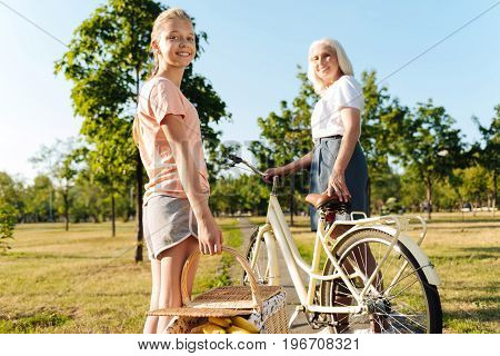 Friendly family. Positive young girl standing with her gradnmother near bicycle and holding a basket for a picnic
