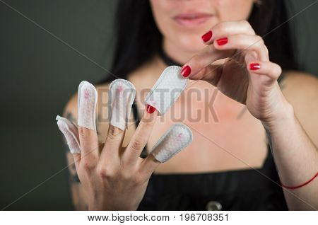 Close up of young woman wearing nails protector in her nails, hand and ideal clean manicure, in a black background.