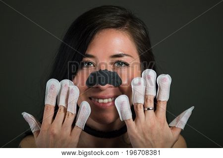 Portrait of young woman wearing nails protector in her nails, hand and ideal clean manicure, in a black background.