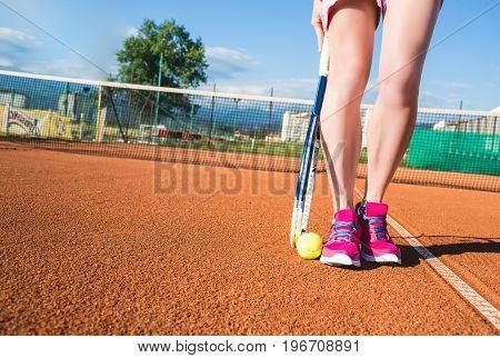Closeup photo of female legs with tennis racket