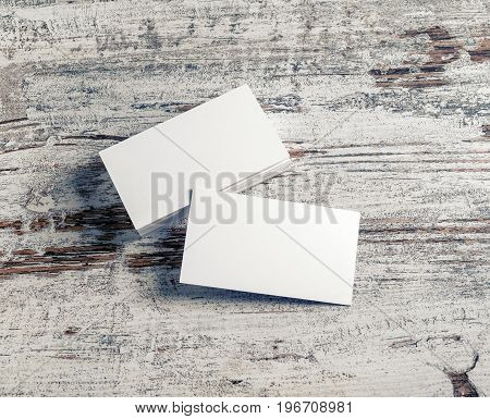 Blank white business cards on vintage wooden background. Template for ID with plenty of copy space.