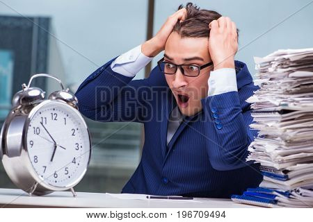 Businessman with pile stack of paper paperwork and an alarm cloc